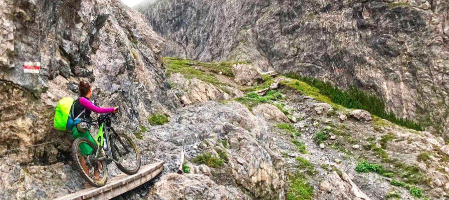 Frau steht neben ihrem e-Mountainbike im Gebirge