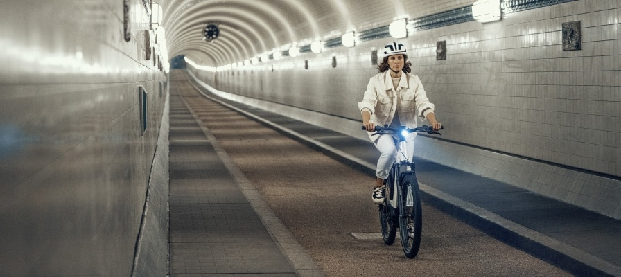 Frau fährt auf dem neuen Nevo3 von Riese & Müller durch eine Unterführung