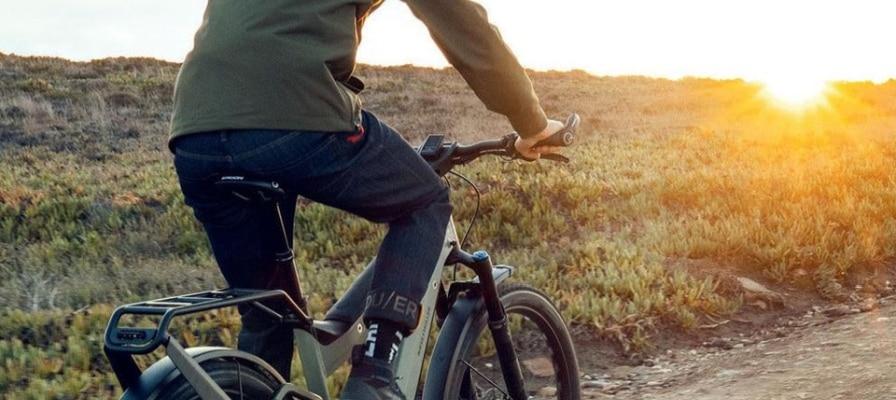 Mann fährt auf e-Bike in den Sonnenuntergang