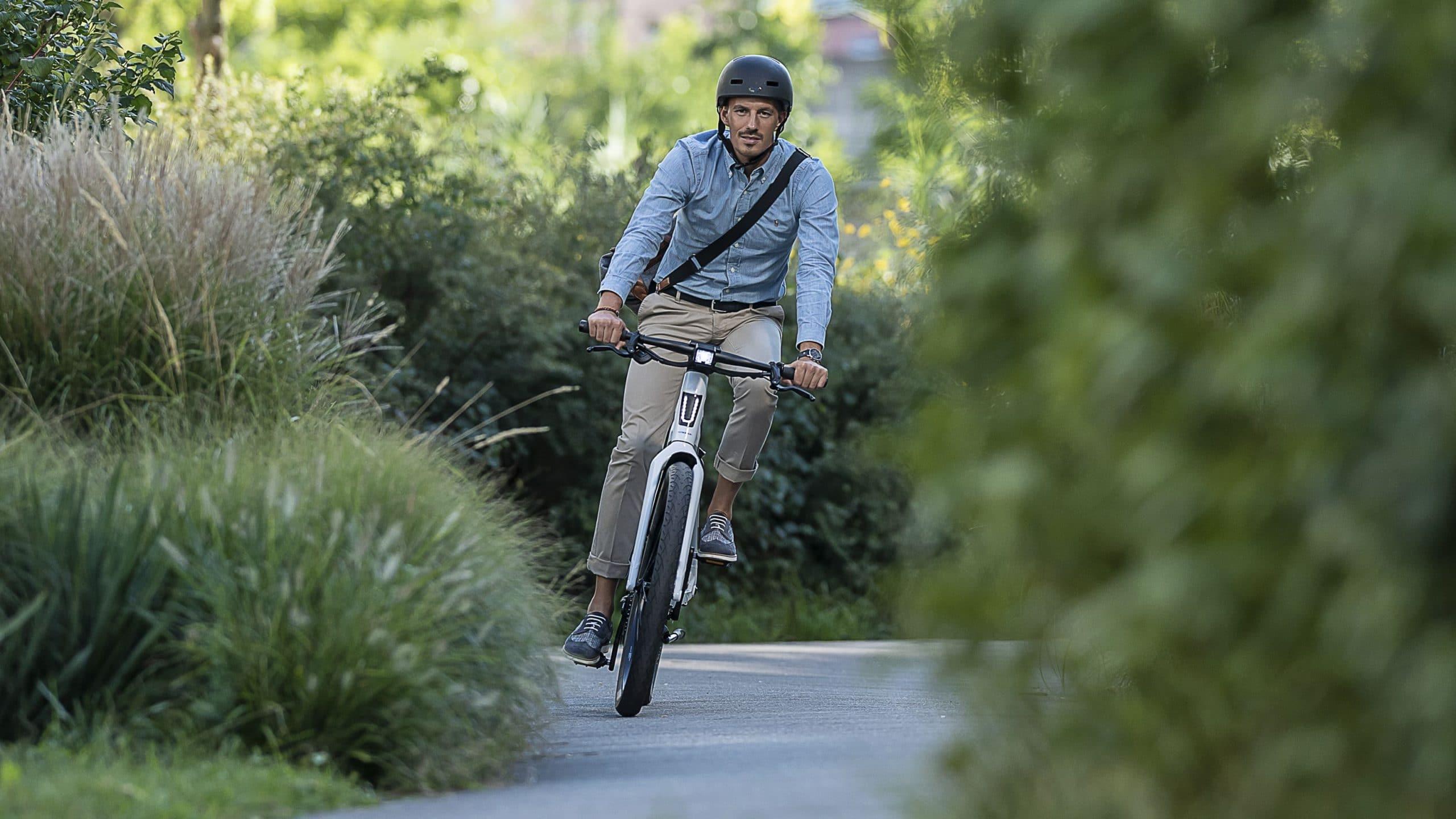 Ein Mann fährt mit seinem Stromer ST3 e-Bike durch Grüne