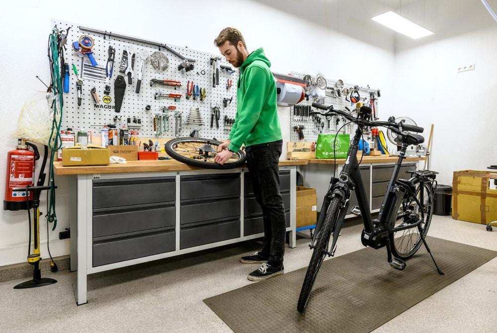 Ein Mitarbeiter arbeitet in der Werkstatt einer e-motion e-Bike Welt