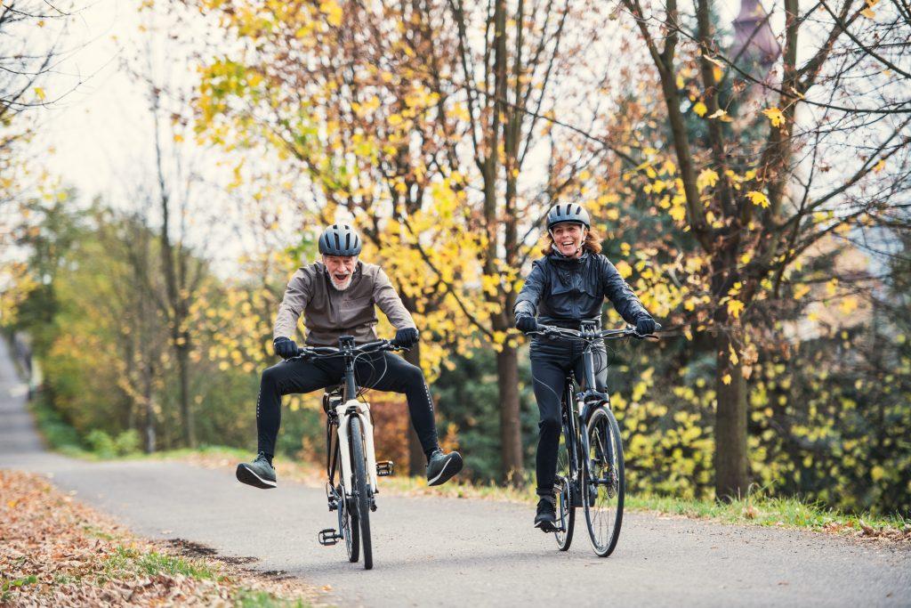 Ein aktives Seniorenpaar mit e-Bikes fahren draußen in der Natur