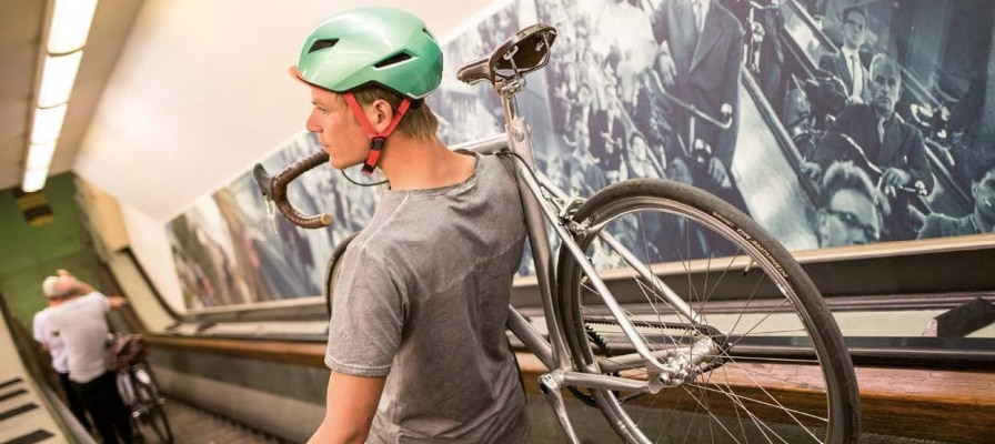 Mann trägt e-Bike die Rolltreppe runter