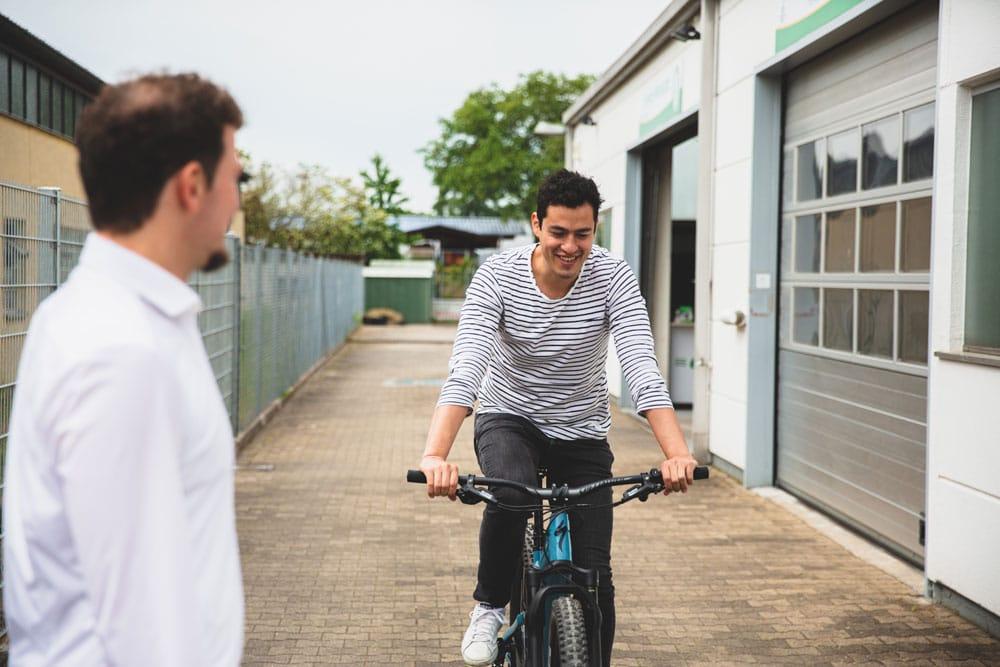 Ein Mitarbeiter der e-motion e-Bike Welt Heidelberg und ein Kunde, der eine Probefahrt mit einem e-Bike macht