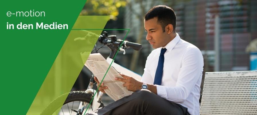 Mann liest Zeitung neben e-Bike