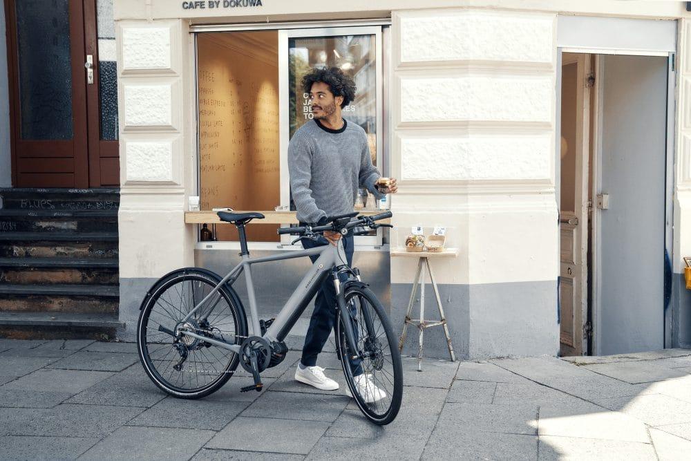 Mann holt sich einen Kaffee to go mit seinem Riese & Müller Roadster