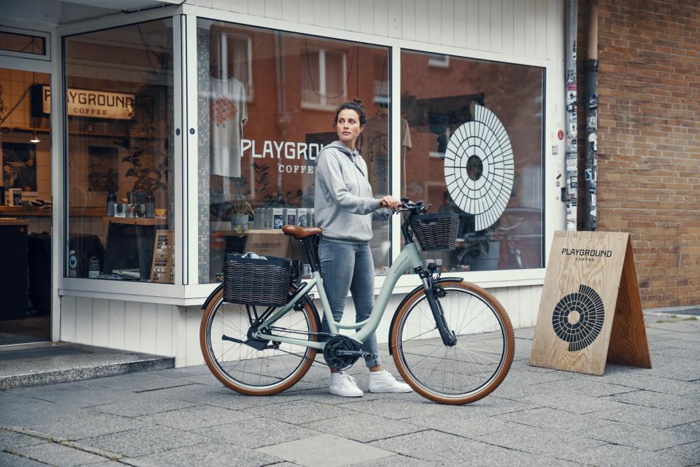Frau steht mit ihrem neuen Riese & Müller Swing3 vor Café