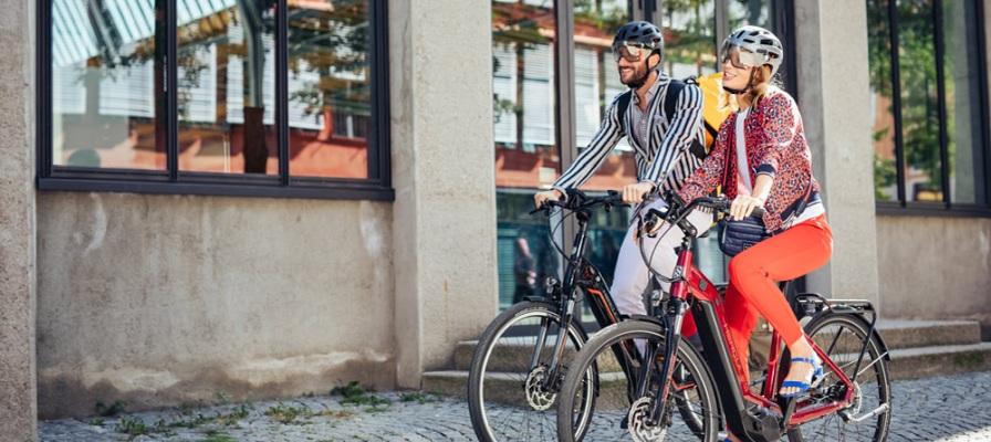 Pärchen fährt auf seinen Hercules e-Bikes durch die Stadt