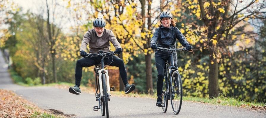 Seniorenpärchen fährt nebeneinander auf seinen e-Bikes durch den Wald