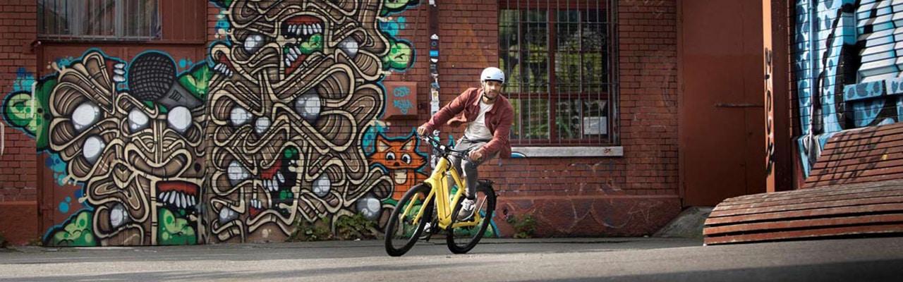 Ein Mann auf einem e-Bike von Stromer vor einer bunten Wand