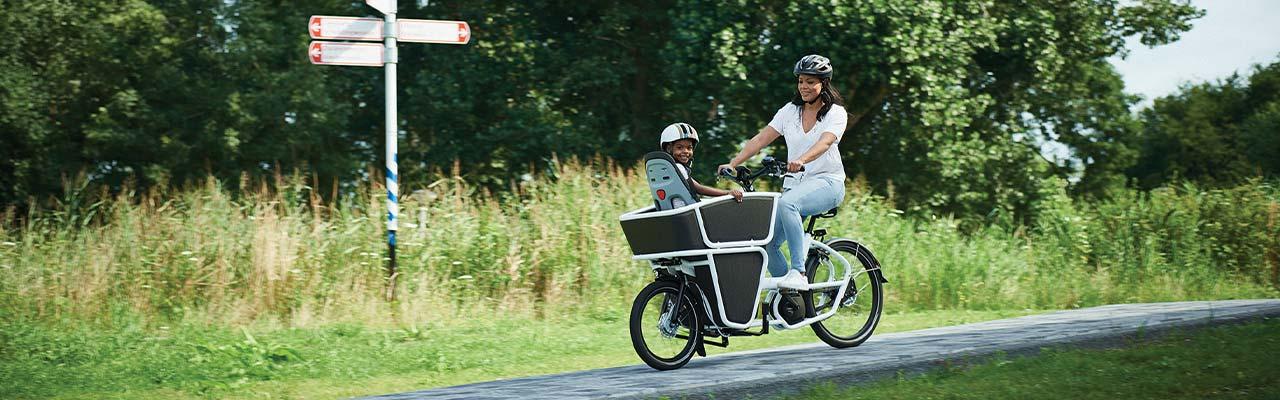 Eine Frau transportiert ihr Kind in einem Urban Arrow Lasten e-Bike