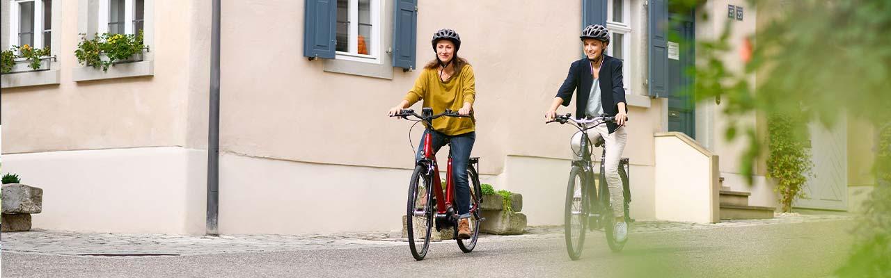 Zwei Frauen fahren auf ihren Winora e-Bikes durch die City