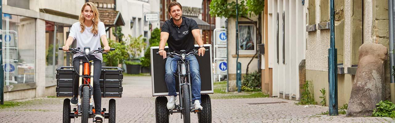 Ein Mann und eine Frau fahren auf ihren XCYC Lasten e-Bikes durch die Stadt.