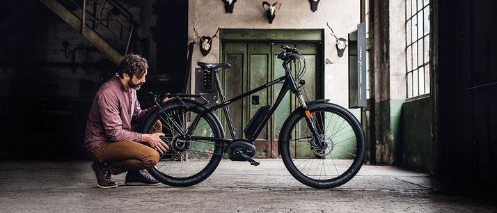 Ein Mann vor einem Riese und Müller e-Bike mit Diamantrahmen