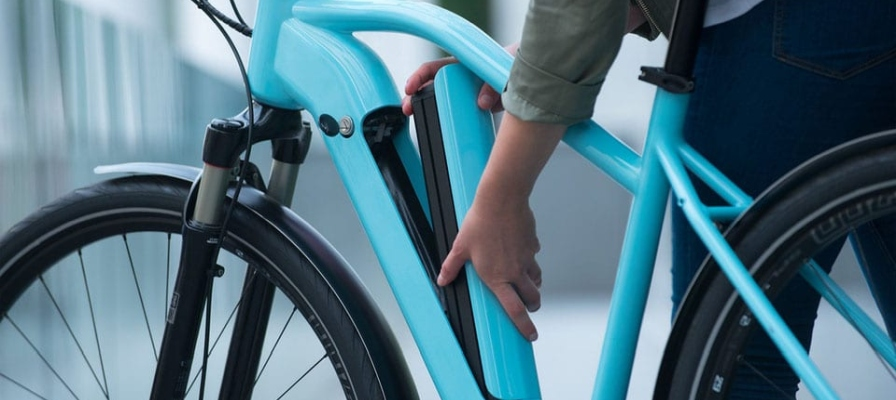 Frau wechselt Akku an blauen e-Bike