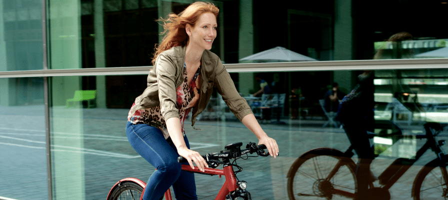 Eine Frau fährt mit ihrem roten e-Bike an einer großen Fensterfläche vorbei