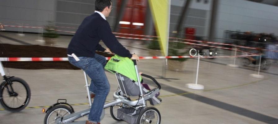 Mann fährt mit dem Dreirad und einem Kind eine abgesperrte Strecke entlang