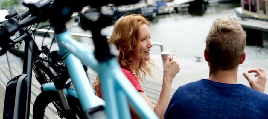 Im Vordergrund steht ein e-Bike, ein Pärchen trinkt gemeinsam Kaffee