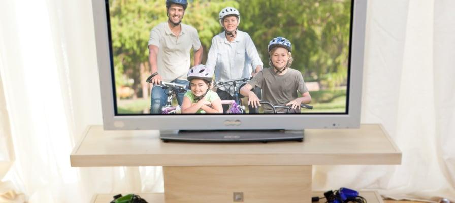 Eine Familie schaut Fernsehen und sieht dort eine Familie auf dem e-Bike