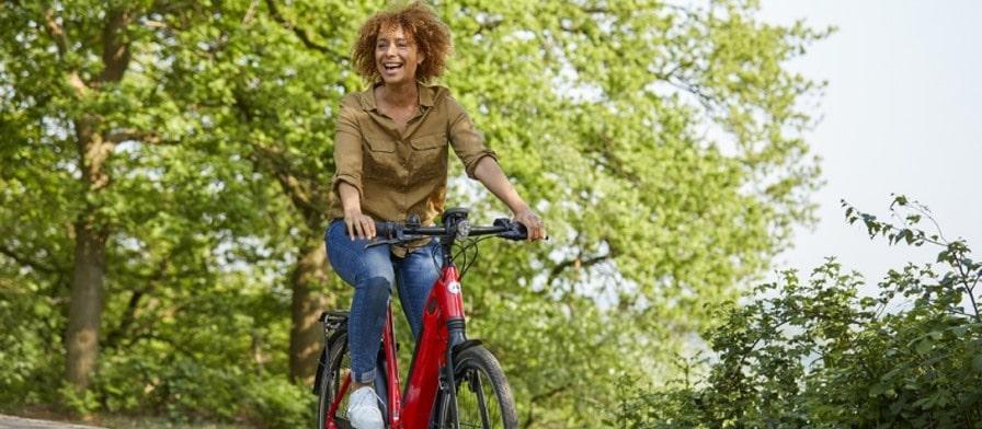 Frau fährt auf ihrem Gazelle e-Bike durch den Wald
