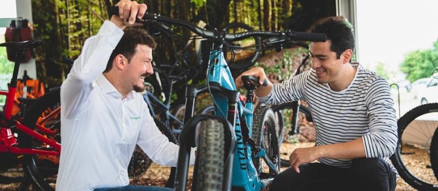 Zwei Männer knien neben einem e-Bike im Verkaufsgespräch in der e-motion e-Bike Welt Heidelberg