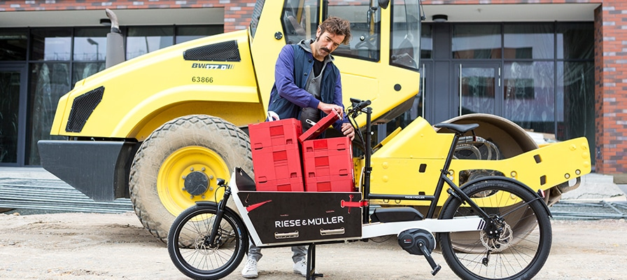 Mann mit Lastenrad vor gelbem Walzfahrzeug mit dem Riese und Müller Packster