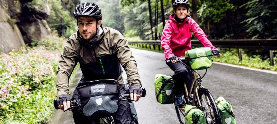 Pärchen fährt mit seinen e-Bikes samt Ortlieb Fahrradtaschen durch den Wald