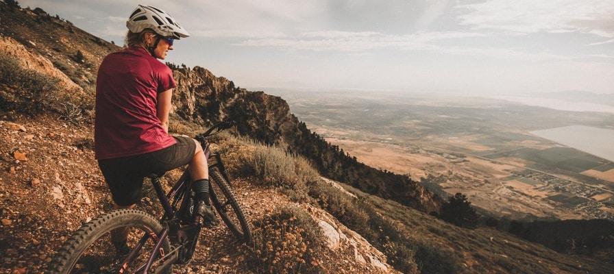Frau genießt den Ausblick vom Berg auf ihrem Specialized Levo