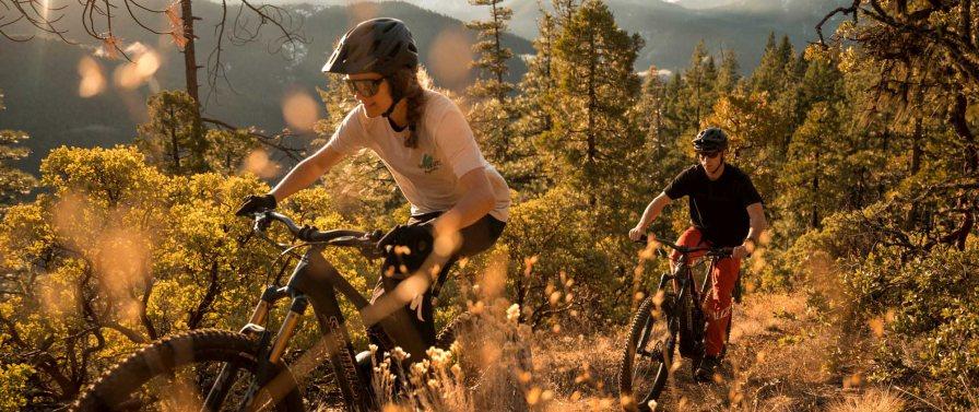 Ein Frau und ein Mann fahren auf ihren Turbo Levo S-Works e-Mountainbikes von Specialized durch einen hügeligen Feldabschnitt