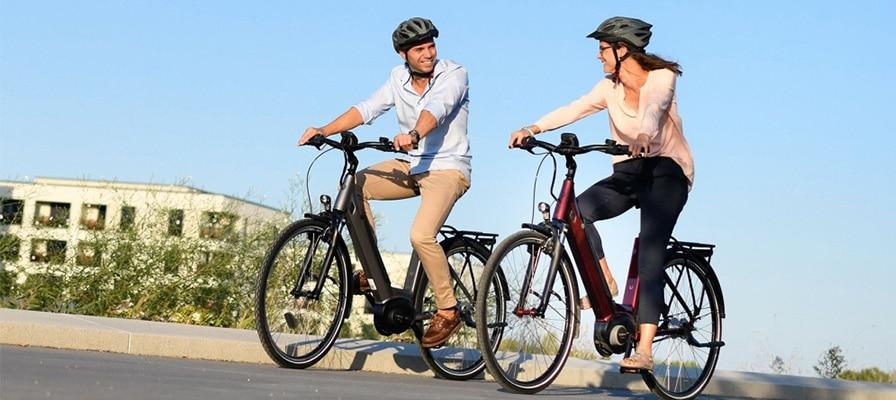 Ein Ehepaar auf zwei e-Bikes im Urlaub