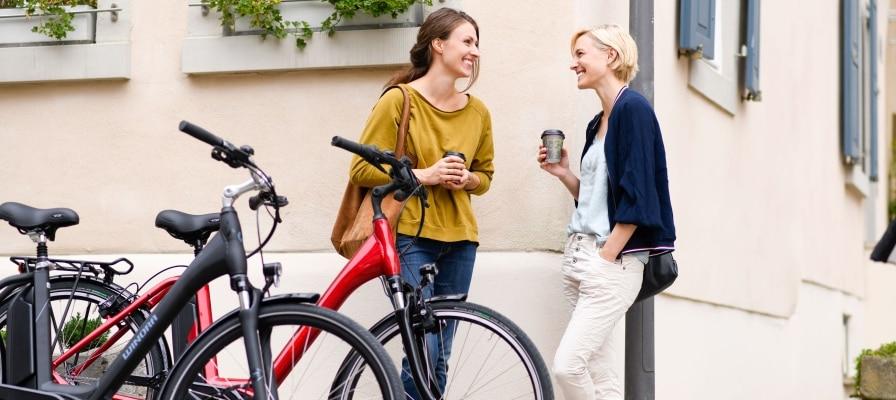Zwei Frauen trinken Kaffee neben ihren Winora Sima e-Bikes