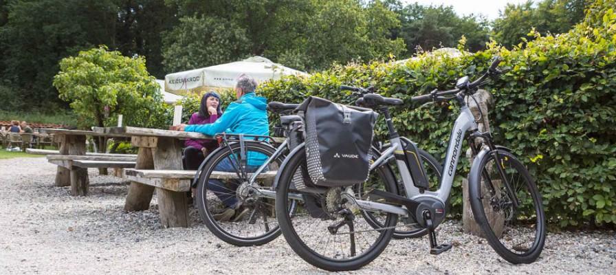 Zwei ältere Menschen sitzen draußen an einem Picknick-Tisch und davor parken zwei e-bikes.