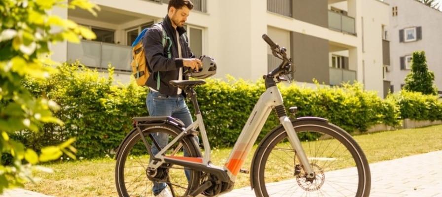 Mann steht vor einem e-Bike und zieht sich einen Helm an.