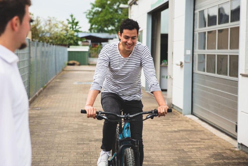 Ein Mann testet ein aktuelles e-Bike aus, ein Mitarbeiter der e-motion e-Bike Welt berät ihn dabei