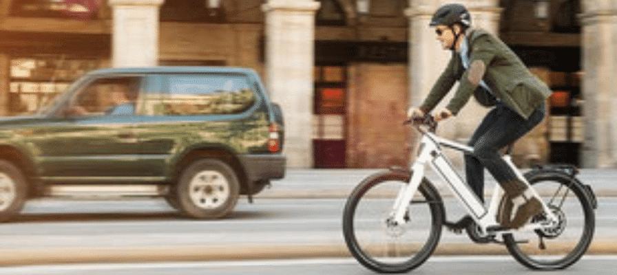 Büroangestellter fährt auf e-Bike durch Stadt