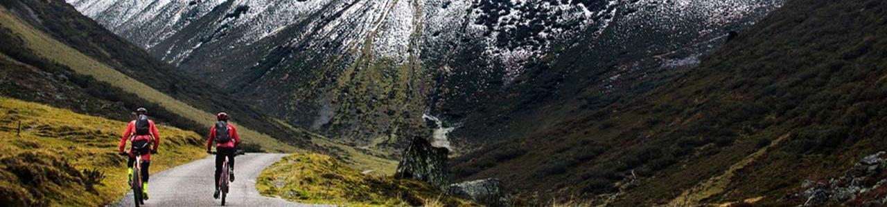 Zwei Personen fahren auf ihrem e-MTB eine bergische Landschaft entlang
