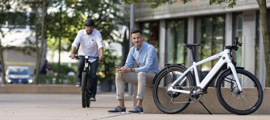 Ein Mann mit Hemd sitzt auf einer Bank und ein anderer Mann fährt mit e-Bike vorbei.