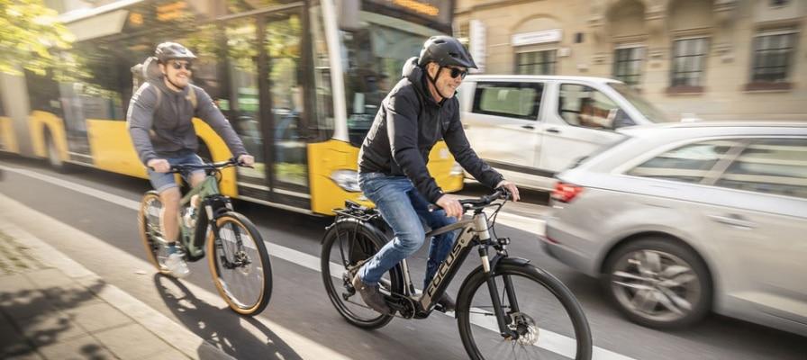 Zwei Männer fahren mit e-Bikes auf befahrener Straße