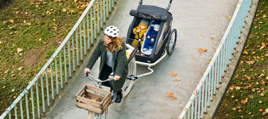 Mutter fährt auf e-Bike mit zwei Kindern im Fahrradanhänger