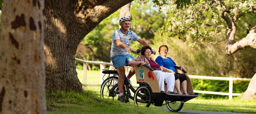 Mann kutschiert zwei ältere Damen im Triobike Taxi