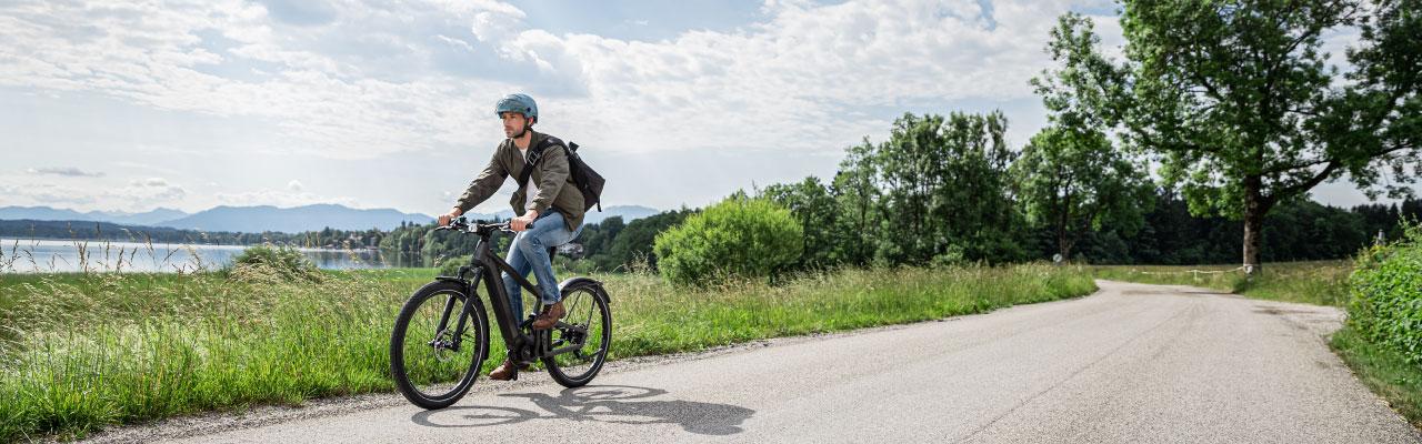 Ein Mann fährt mit seinem Riese und Müller e-Bike durch die Natur