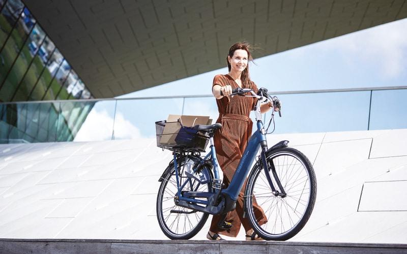 Eine Frau schiebt ihr e-Bike von Gazelle