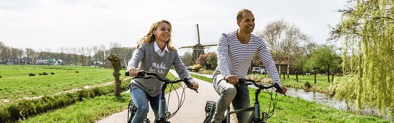 Ein Paar fährt glücklich mit den komfortablen City e-Bike Modellen Entour E+ durch eine sommerliche Landschaft