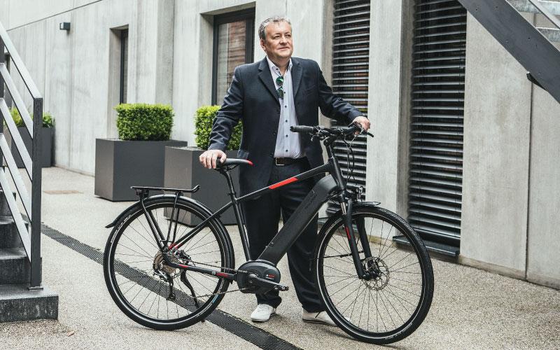 Mann steht neben Raleigh XXL e-Bike