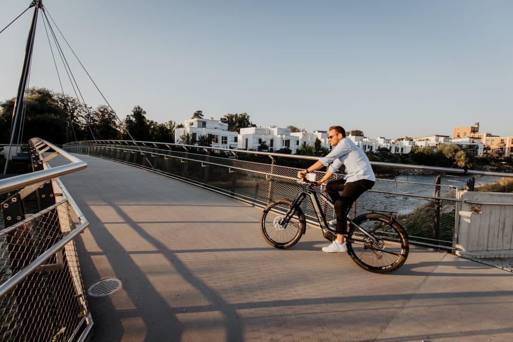 Mann fährt auf seinem M1 Erzberg GT über eine Brücke