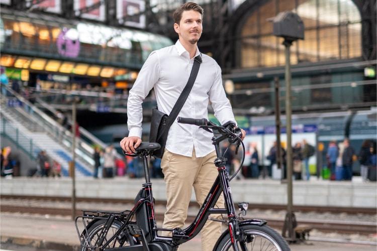 Mann steht mit Kompakt e-Bike am Bahngleis