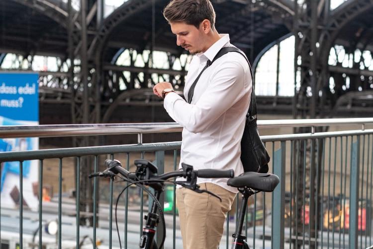Mann wartet mit e-Bike am Bahnhof