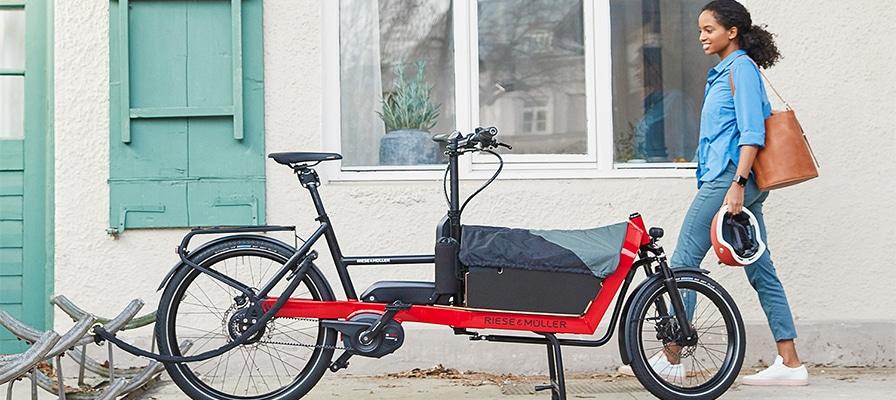 Eine Frau auf dem Weg zu ihrem Riese und Müller Lasten e-Bike