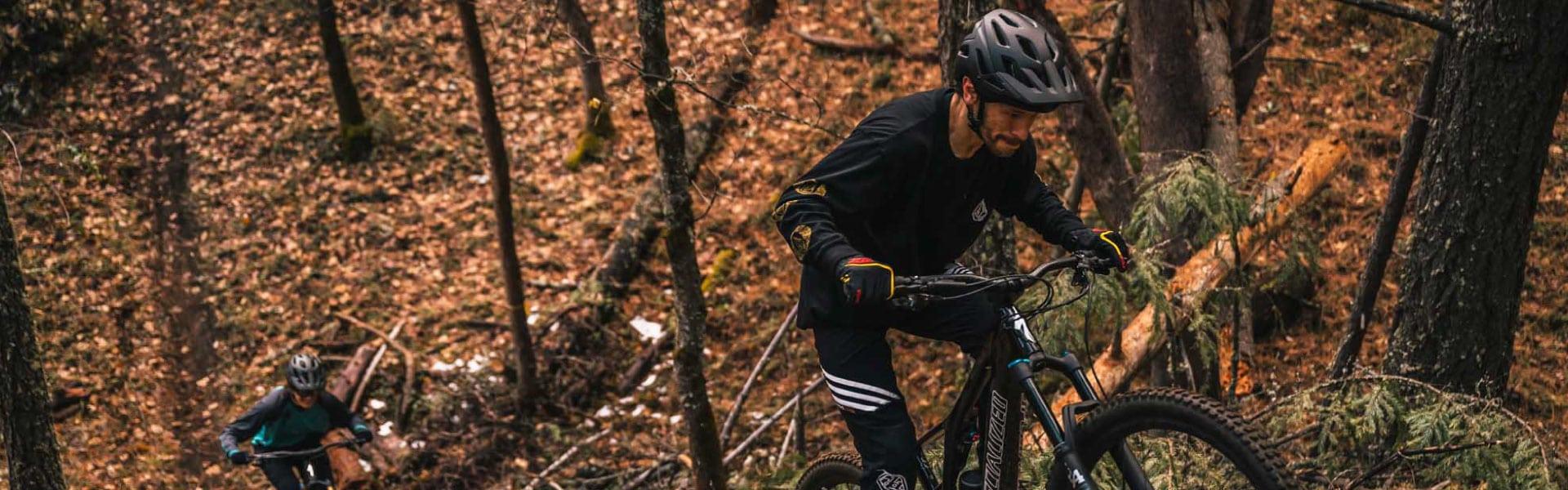 Zwei Personen fahren mit ihren Specialized e-Mountainbikes durch den Wald