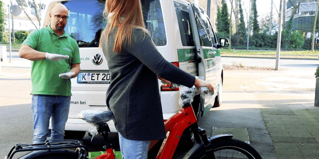 Ein e-Bike wird unter Wahrung der Corona Hygienemaßnahmen kontaktlos an eine Kundin übergeben